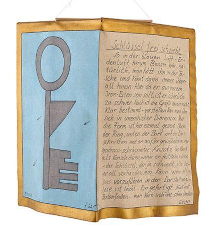 Bemaltes Stoffstück mit Schlüssel auf blauem Grund und handschriftlich verfasstem Text, mittig nach oben geknickt