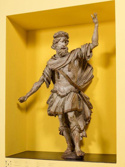 Überlebensgroße, monochrom hell gefasste Skulptur des Samson als Kanzelträger in römisch-antiker Soldatenbekleidung, seitliche Ansicht.