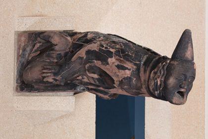 Sandsteinfigur eines Mannes mit Spitzhut als Wasserspeier, Ansicht von der linken Seite.