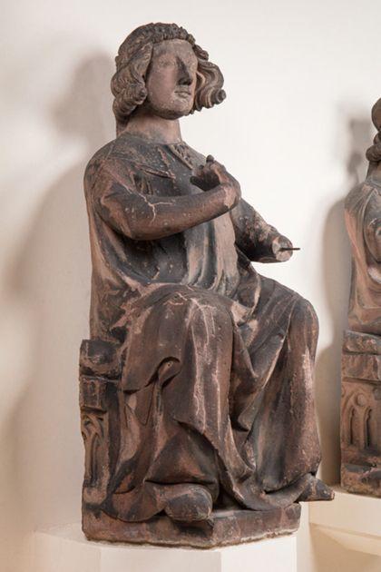 Sandsteinfigur eines sitzenden Grafen mit Blütenkranz, Seitenansicht von links.
