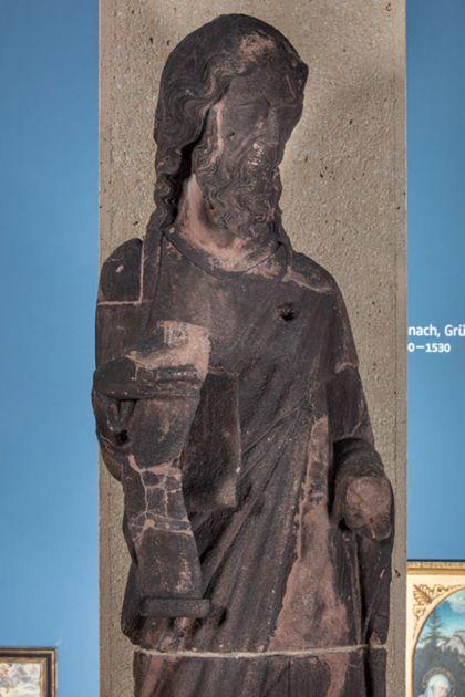 Weit überlebensgroße Sandsteinfigur eines schmalen, in den Proportionen gelängten Propheten mit Spruchband, Detail des Oberkörpers.
