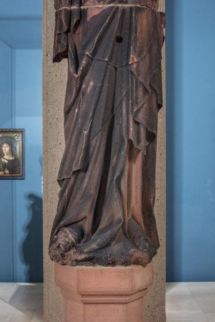 Weit überlebensgroße Sandsteinfigur des schmalen, in den Proportionen gelängten Propheten Moses, Ansicht der unteren Partie der Skulptur.