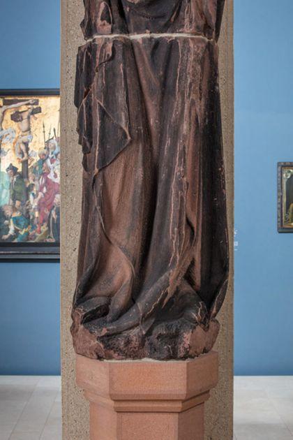Weit überlebensgroße Sandsteinfigur eines schmalen, in den Proportionen gelängten Propheten mit Spruchband, Detail der unteren Partie der Skulptur.