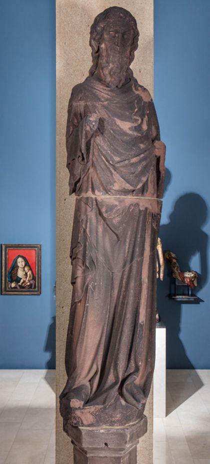 Weit überlebensgroße Sandsteinfigur eines schmalen, in den Proportionen gelängten Propheten ohne Attribute.