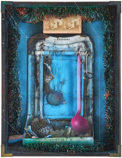 Objektkasten mit an einer Stange montierten Küchenutensilien und Schlüssel, gerahmt von grün-roter Girlande, in dunklem Rahmen