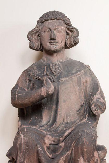 Sandsteinfigur eines sitzenden Grafen mit Blütenkranz, Detail des Oberkörpers.