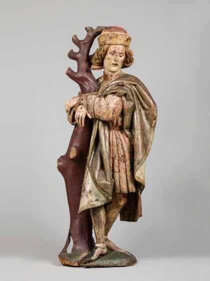 Gefasste Holzskulptur des an einen kahlen Baumstamm gefesselten heiligen Sebastian in vornehmer Gewandung.