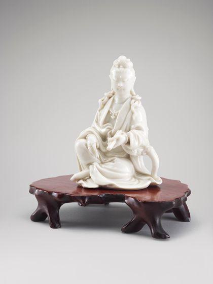 Auf einem hölzernen Sockel sitzt aus weißem Porzellan eine Figur. Dargestellt ist Kuan-yin, die weibliche Form des indischen Bodhisattvas Avalokiteshvara.