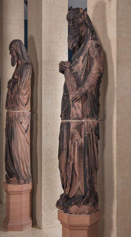 Weit überlebensgroße Sandsteinfigur eines schmalen, in den Proportionen gelängten Propheten mit Spruchband, Seitenansicht von rechts.