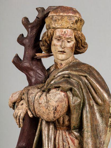 Gefasste Holzskulptur des an einen kahlen Baumstamm gefesselten heiligen Sebastian in vornehmer Gewandung, Detail des Oberkörpers.