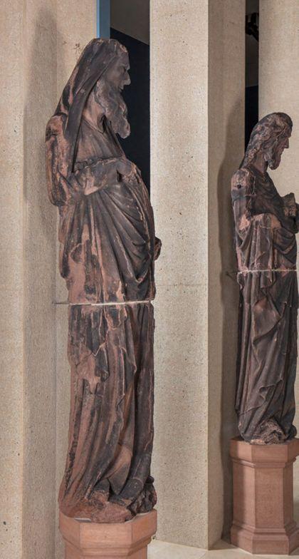 Weit überlebensgroße Sandsteinfigur eines schmalen, in den Proportionen gelängten Propheten mit Spruchband, Seitenansicht von links.