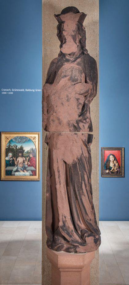 Stark beschädigte, überlebensgroße Sandsteinfigur eines schmalen, in den Proportionen gelängten Propheten mit Kappe.