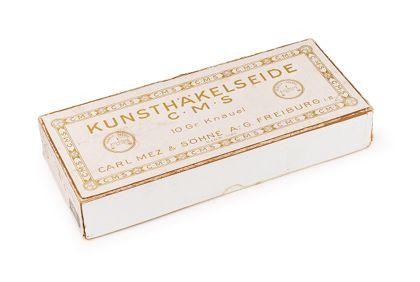 Weiße historische Schachtel mit ockerfarbenem Aufdruck.