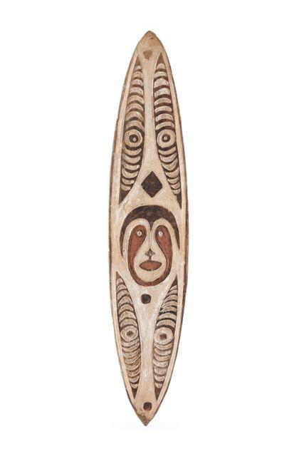 Ahnen- oder Gobe-Brett aus hellem, leichtem Holz., das auf der Vorderseite reich beschnitzt in weißer Grundierung gehalten ist und in dunkelbrauner und roter Bemalung die stilisierte Darstellung eines menschlichen Gesichtes zeigt.