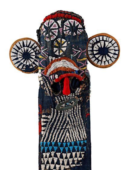 Kopfmaske aus dunkelblauem, gefüttertem Stoff. Vorne und hinten befinden sich lang herabhängende breite Stoffbahnen mit roter Einfassung und oben zwei scheibenförmige Ohren. Die Maske ist reich bestickt mit Perlen in den Farben weiß, lila, hellblau und gelb.