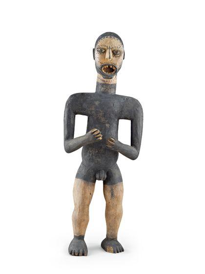 Männliche Figur aus hellem Holz, schwarz bemalt. Auffallend ist der ovale offene Mund mit spitzen Zähnen.