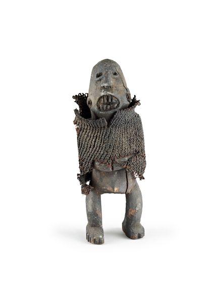 Stehende Figur aus Holz, mit übergezogenem geflochtenem Schlauch. Die Hände sind vor dem Leib zusammengelegt. Das Holz ist schwärzlich patiniert.