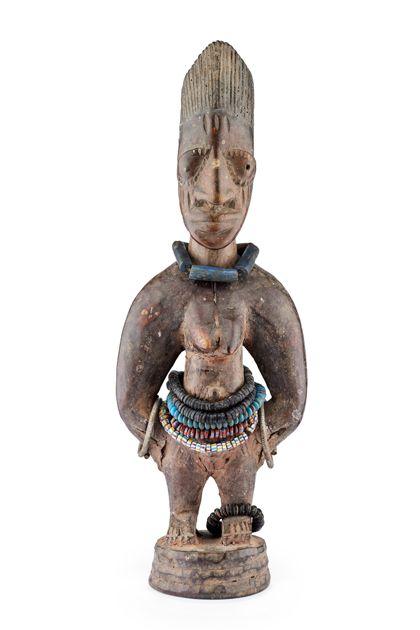 Ibedji-Figur mit hoher Riffelfrisur und Gesichtsnarben. Die Figur ist geschmückt mit vier Glasperlenschnüren, zwei Ketten aus Schildpattscheibchen und zwei Armreifen aus Eisen.