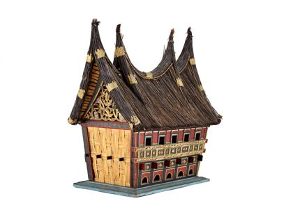 Modell eines Hauses mit rechteckigem Grundriss, dessen Wände nac h oben hin breiter verlaufen und aus Bast gearbeitet sind. Der Dachfirst ist zu vier Wipfeln aufgebogen. Die Frontseite des Hauses besteht aus grün und rot bemaltem sowie mit Goldbronze verziertem Holz.
