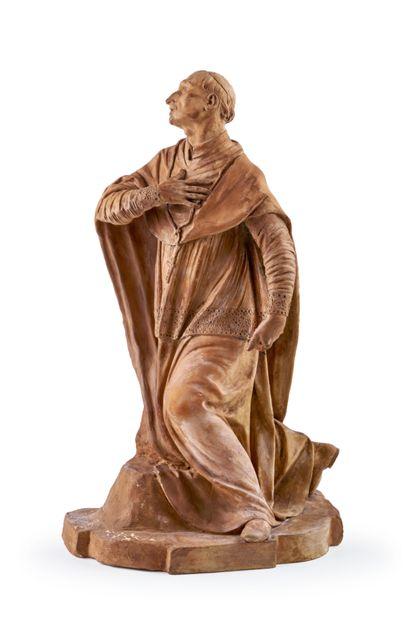 Skulptur eines knienden Heiligen in Andachtshaltung.