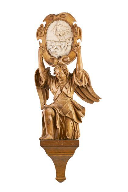 Ein geschnitzter Engel kniet und hält ein Medaillon mit einem Bild der Himmelfahrt Christi.