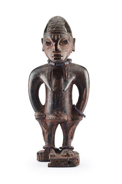 Ibeji Figur mit kronenartiger Kopfbedeckung, die hohl ist. Auf der Stirn sind kurze, von den Schläfen über die Wangen lange abgeknickte Schmucknarben eingeschnitzt. Über der Brust und am Bauch befinden sich lange vertikale Schmucknarben. Die Figur trägt am linken Arm und an beiden Füßen Perlenketten aus kleinen blauen Perlen mit rot-weißen Strichen. Am rechten Fuß mit Sockel ist ein Stück Holz ausgebrochen.