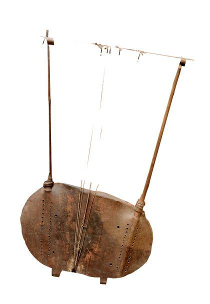 Saiteninstrument aus einem beckenförmigen Resonanz-Körper der mit Fell bespannt ist, und einem trapezartigen Gestänge. Über einen Steg sind sechs Saiten zu dem Querholz gespannt (Schnursaiten).