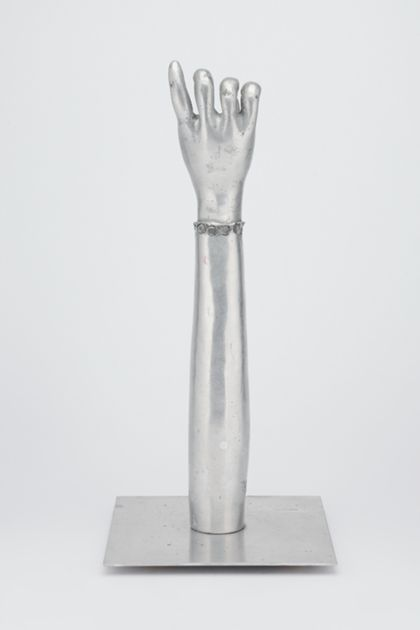 Ausgestreckter Arm mit halb geschlossener Hand aus poliertem Aluminium, auf einer Platte stehend, Vorderansicht