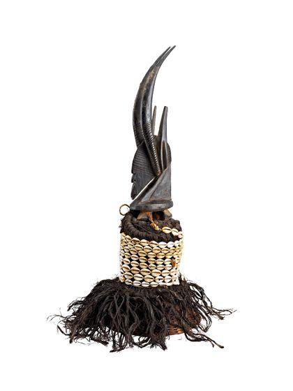 Antilopen-Aufsatzmaske bestehend aus einem hutartigen geflochtenen Teil, der mit schwarz gefärbtem Bast bedeckt ist und nach unten in Fransen ausläuft. Der obere Teil ist mit Kaurischnecken besetzt. Darauf befindet sich ein Antilopenkopf mit senkrecht stehendem Gehörn.
