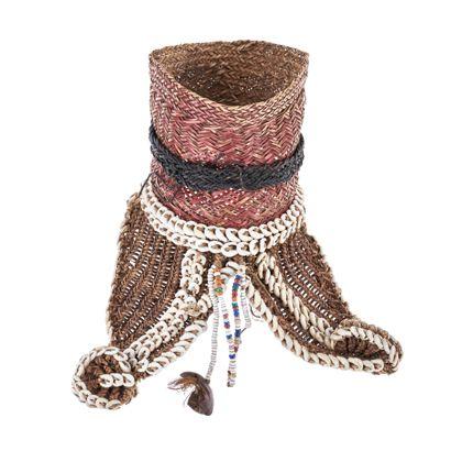 Oberarmschmuck aus Rotang-Geflecht, das mit Nassa-Schnecken besetzt und dem kleine Perlschnüre mit einer Fruchtschale angehängt ist.