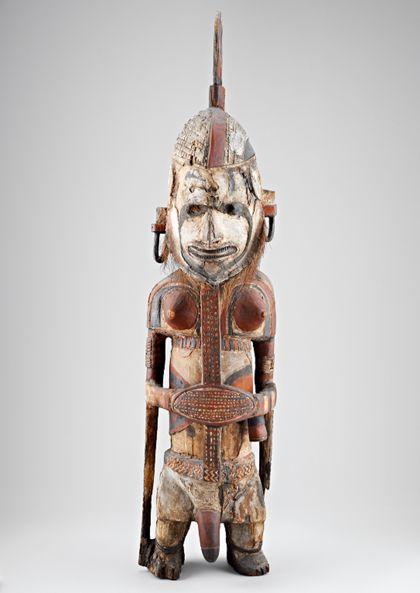 Zweigeschlechtliche Figur mit Kopfschmuck, die teilweise mit Kreide-Gipsgrund überzogen und rot und schwarz bemalt ist.