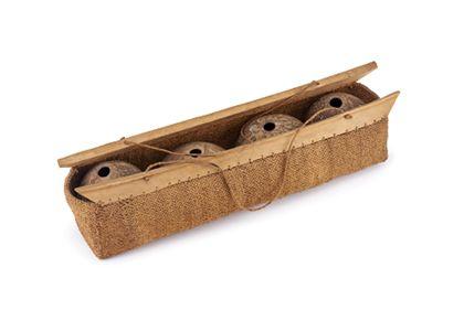 Vier Kokosnussschalen in einem länglichen Korb, der aus Kokosfaserschnur geflochten ist und mit zwei Holzstielen am Rand versehen ist.
