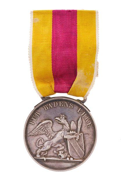 Historische Verdienstmedaille mit Landeswappen an einem gelb-roten Band.