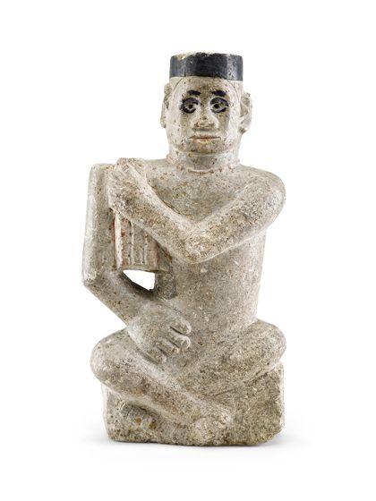 Hockende menschliche Figur aus Seifenstein. Der linke Arm liegt vor der Brust, die Hand hält eine auf der rechten Schulter liegende Decke. Augen und Kappe sind schwarz bemalt.