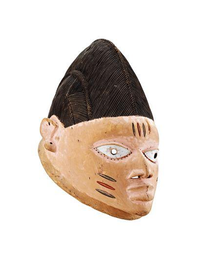 Stülpmaske mit hellem Gesicht und kappenartiger, schwarzbrauner Frisur, die mit Kerbschnitten in einer Art Grätenmuster versehen ist. Auf Stirn und Wangen je drei Narben eingeschnitzt.