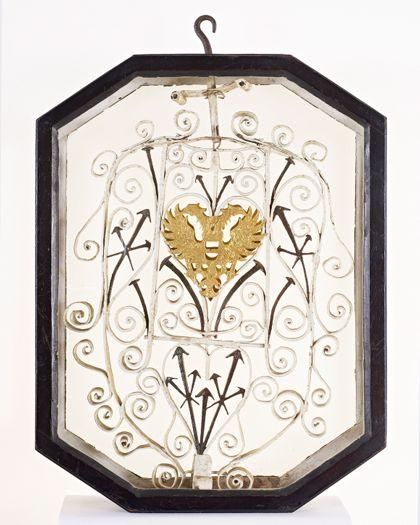 Rahmen um Metallgitter, in das Gitter eingelassen sind Nägel und ein goldener Doppeladler