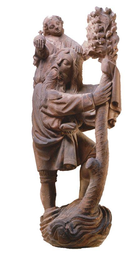 Sandsteinfigur des heiligen Christophorus, der auf einen Frucht tragenden Baumstamm gestützt durch einen Wellenberg schreitet und das Christuskind auf seiner rechten Schulter trägt.