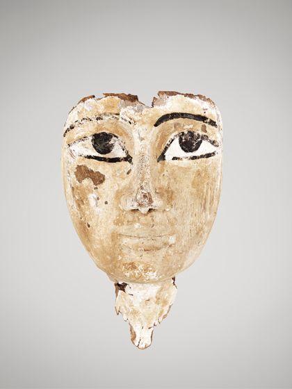 Fragment einer Holzmaske, die mit Stuck überzogen und einem Gesicht bemalt ist.