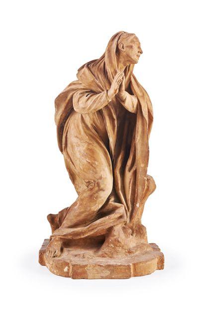 Holzskulptur einer knienden Heiligen.