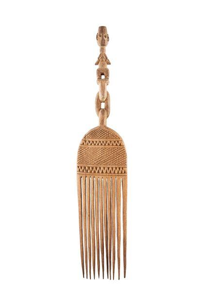 Langer Kamm aus Holz mit eingeschnittenen Ornamenten. Der Griff stellt eine stehende menschliche Figur dar.
