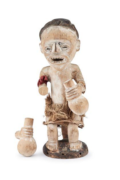 Sitzende menschliche Figur aus Holz auf scheibenförmigem Sockel. In den Händen hält die Figur je eine Flasche. Die Figur ist gearbeitet aus hellem Holz. Sie weist Reste weißer Bemalung und schwarzer Bemalung auf und hat einen Schurz aus Pflanzenfasern umgebunden. Die Figur ist beschädigt.
