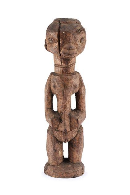 Roh gearbeitete weibliche Figur aus Holz mit rundem Kopf. Die Augen befinden sich weit seitlich, die Nase-Mund Partie ist in dreieckiger Form zusammengefasst. Über dem linken Auge befindet sich Narbenschmuck. Die kurzen Beine ohne Füße stehen auf einem runden, nach oben konvexen Sockel. Seitlich an der Figur befinden sich Henkelarme, ohne Hände.