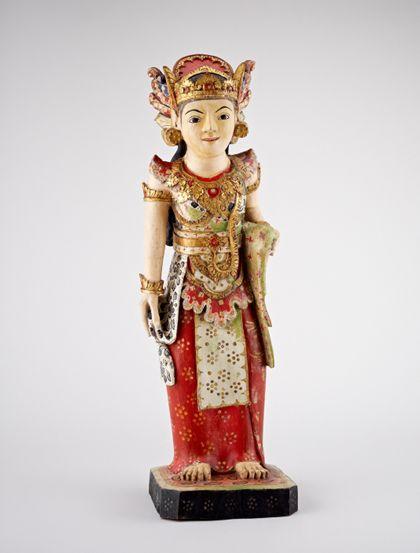 Die hölzerne Figur zeigt eine Göttin in einem reich bemalten wie verziertem Gewand in den Hauptfarben rot, grün und weiß, geschmückt mit einer aufwendigen Kopfbedeckung und vergoldeten Applikationen.