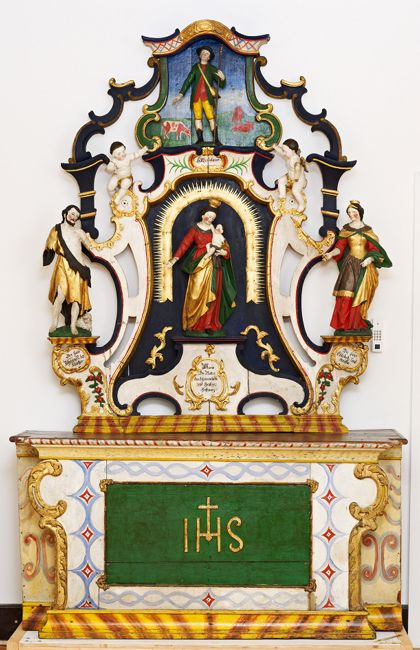Farbig gestalteter Altar mit Maria und Jesuskind in der Mitte von verschiedenen Heiligenfiguren und Engeln umgeben.