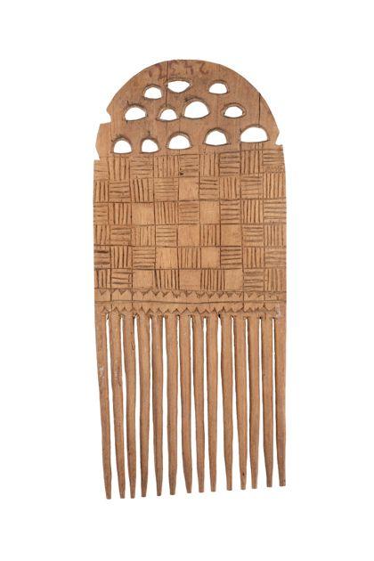 Brettförmiger Kamm aus braunem Holz mit eingeschnittenen Ornamenten, die schachbrettartikg, längst- und querschraffiert sind.