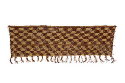 Eine Matte aus braunen und naturfarbenen  Faserschnüren in einer Art Schlingtechnik hergestellt, an deren Rand kleine Fransenbüschel angeknüpft sind.