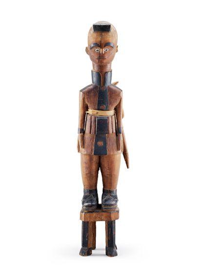 Figur aus rötlichem Holz. Die Figur trägt ein Gewehr im Gürtel und steht auf einem Hocker ähnlichen Sockel.
