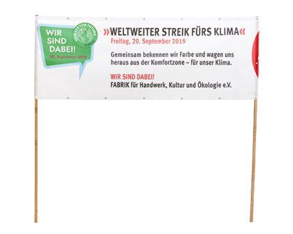 """Transparent mit der Aufschrift """"Weltweiter Streik fürs Klima"""", das außen an zwei Holzstielen befestigt ist."""
